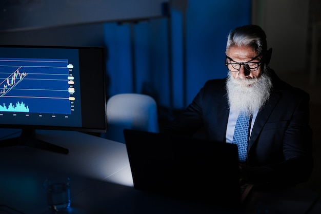 Homme d'affaires senior travaillant la nuit à l'intérieur du bureau de la société fintech