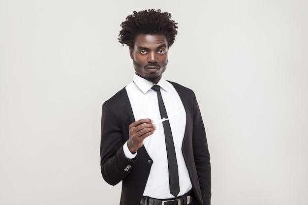 Homme d'affaires sérieusement afro regardant la caméra et attendez. prise de vue en studio