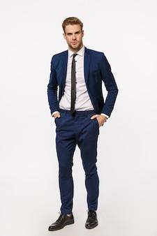 Homme d'affaires sérieux et affirmé en costume classique, main dans la main en pantalon, air confiant, bureau de préparation, accord commercial, contrat important