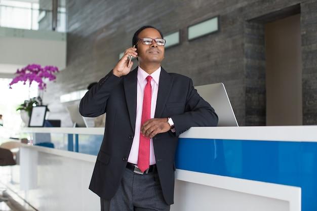 Homme d'affaires sérieux appelant au téléphone lors de la réception