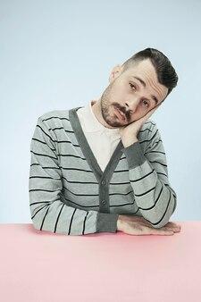 Homme d'affaires sérieux, ennuyé et terne assis à table. le portrait dans un style minimalisme