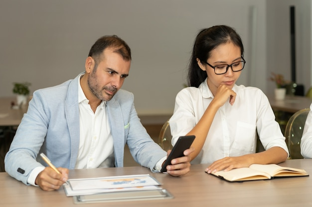 Homme d'affaires sérieux et femme travaillant au bureau dans le bureau