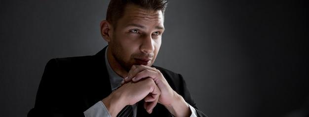 Homme d'affaires sérieux avec les mains sur le menton à l'arrière-plan de la bannière sombre