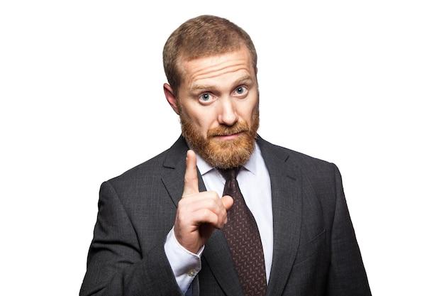 Homme d'affaires sérieux ne montrant aucun signe avec son doigt sur un fond blanc. tourné en studio, isolé..