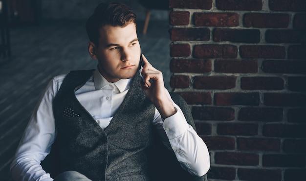 Homme d'affaires sérieux, parler au téléphone en position couchée dans un fauteuil vêtu d'un costume en toute confiance