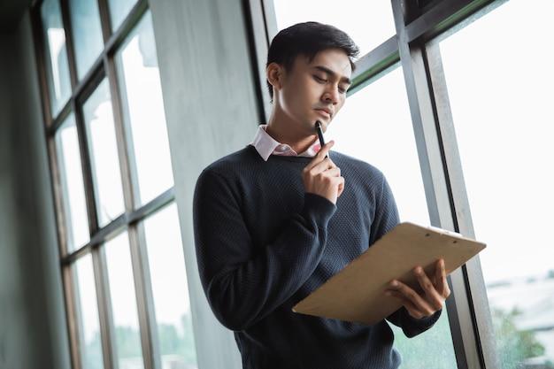 Homme d'affaires sérieux pensant regarder sur le presse-papiers sur ses mains avec mettre un stylo à bille sur le menton