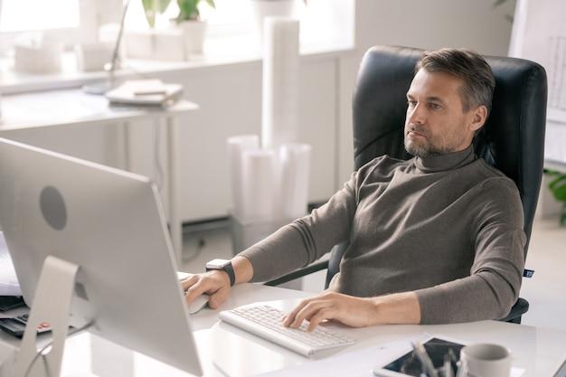 Homme d'affaires sérieux se concentrant sur le travail assis dans un fauteuil par un bureau en face de l'écran de l'ordinateur au bureau