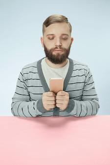 Homme d'affaires sérieux avec téléphone portable assis à la table