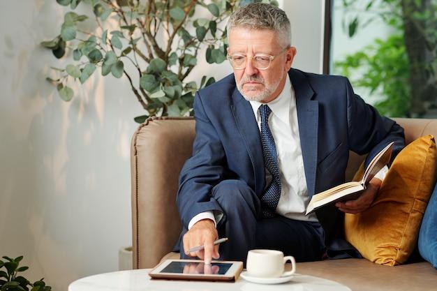 Homme d'affaires sérieux, vérification du calendrier sur tablette lors du remplissage du journal avec des plans pour le mois à venir