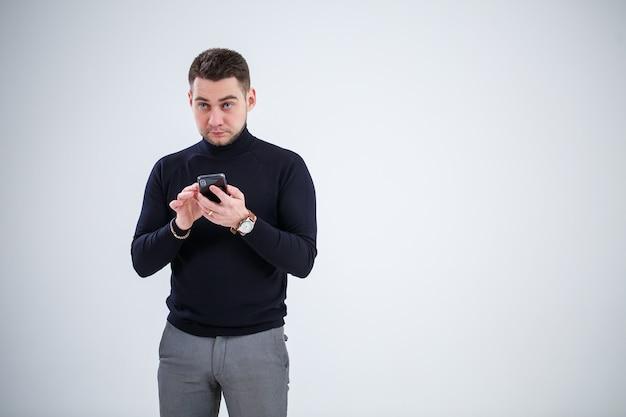 Un homme d'affaires sérieux en vêtements noirs découvre des questions importantes par téléphone. notion de jour ouvrable