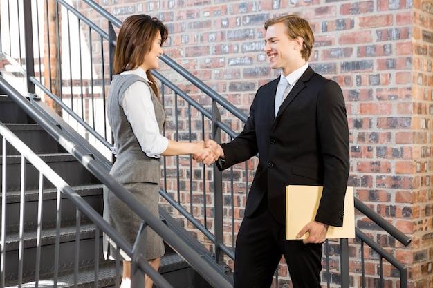 Homme affaires, serrer main, femme affaires, sur, escalier