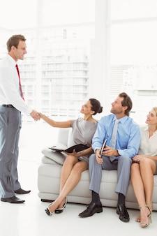 Homme affaires, serrer main, femme, outre, gens, attente, interview