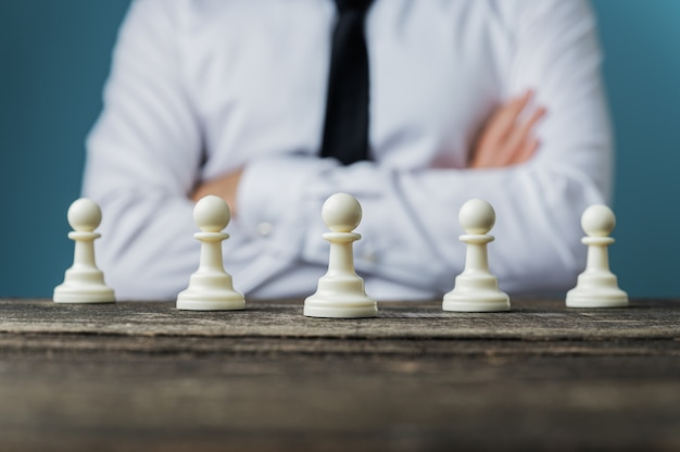 Homme d'affaires avec ses bras croisés assis derrière un bureau avec des pièces de pion d'échecs placées dessus