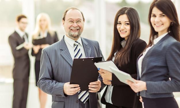 Homme d'affaires et ses deux assistants avec des documents sur le fond du bureau.