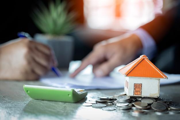 Homme d'affaires signe un contrat derrière le modèle architectural de la maison