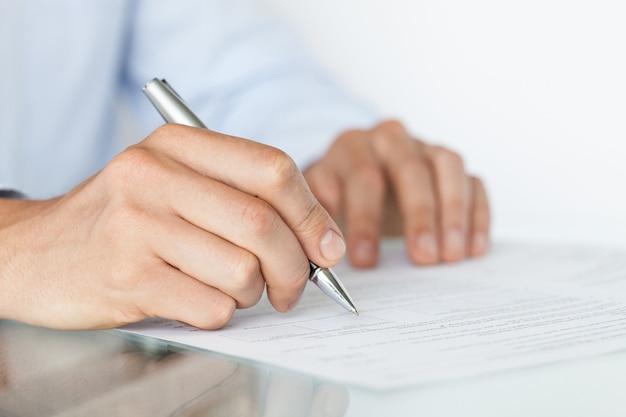 L'homme d'affaires signe un contrat, les détails du contrat commercial