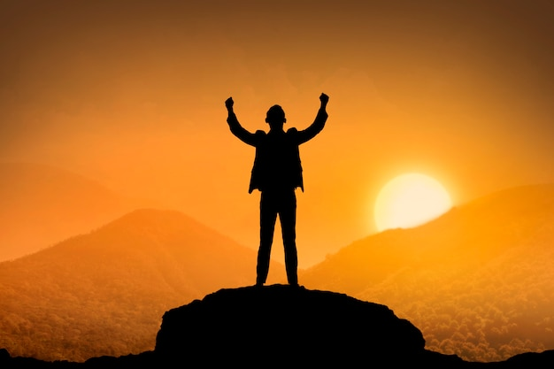Homme d'affaires de silhouette debout en haut de la montagne
