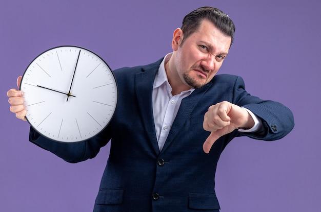 Homme d'affaires slave adulte mécontent tenant l'horloge et le pouce vers le bas