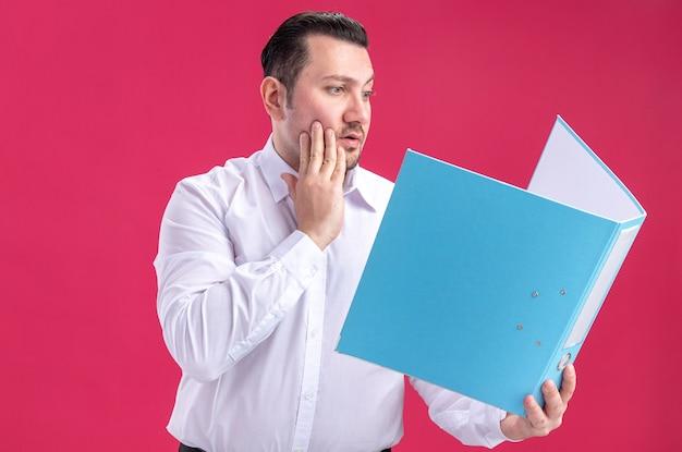 Homme d'affaires slave adulte surpris tenant et regardant le dossier de fichiers