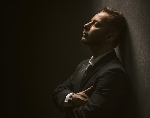 Homme d'affaires solitaire fatigué se tient les yeux fermés avec les bras croisés.