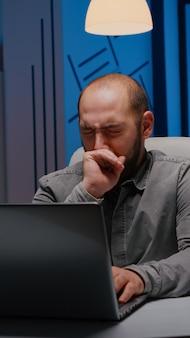 Homme d'affaires somnolent épuisé bâillant tout en travaillant à la date limite du projet de gestion