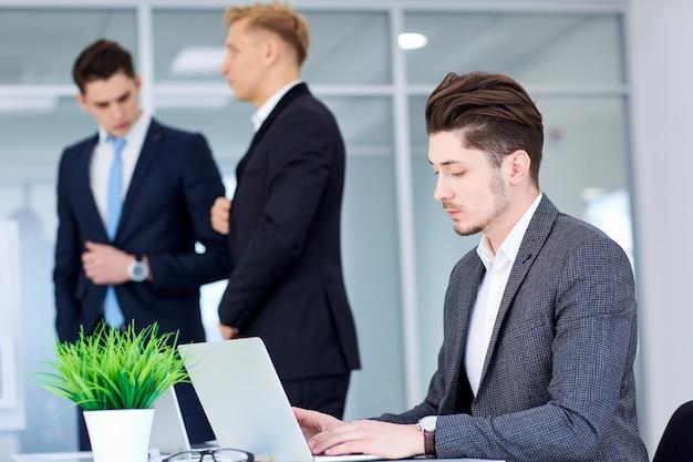 Homme d'affaires à son bureau travaillant sur un ordinateur portable en arrière-plan bu