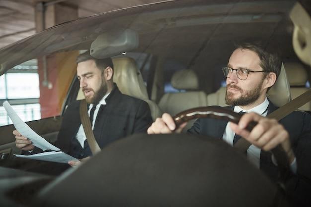 Homme d'affaires et son chauffeur dans la voiture