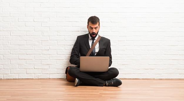 Homme d'affaires avec son ordinateur portable assis sur le sol avec une expression faciale surprise et choquée