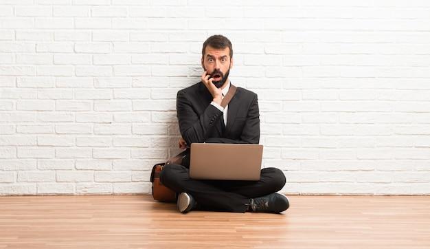 Homme d'affaires avec son ordinateur portable assis sur le sol surpris et choqué tout en regardant à droite