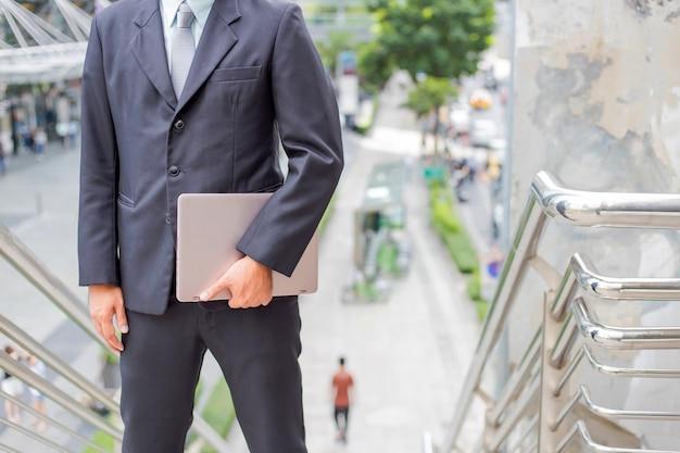 Homme d'affaires avec son ordinateur portable qui monte les escaliers en heure de pointe pour travailler. dépêche-toi.