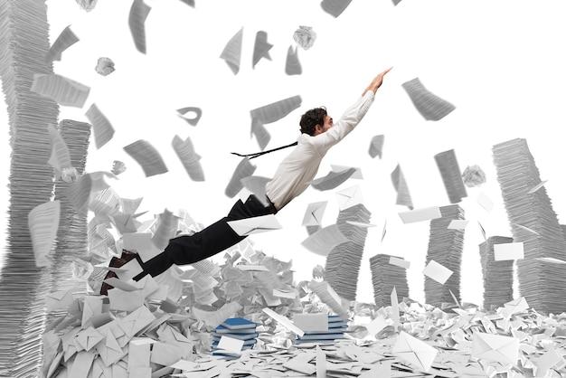 Homme d'affaires sort d'une pile de feuilles de papier