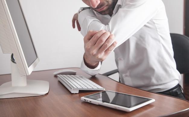 Homme d'affaires souffrant de douleurs au coude au bureau.