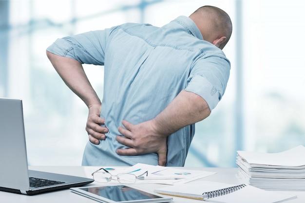Un homme d'affaires souffrant de maux de dos pèche dans un bureau. concept de soulagement de la douleur