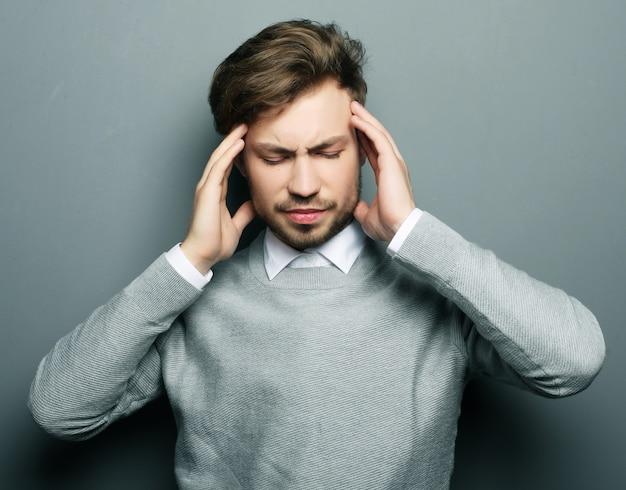 Homme d'affaires a souligné l'inquiétude des maux de tête de pression isolé sur gris b