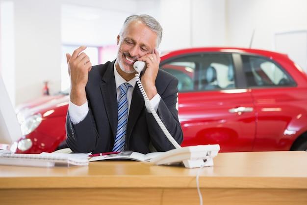 Homme d'affaires souriant à l'aide d'un ordinateur portable sur le téléphone