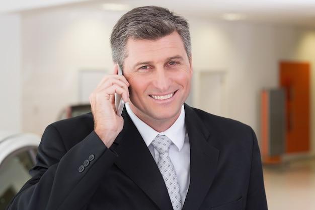 Homme d'affaires souriant, appelant avec son téléphone portable