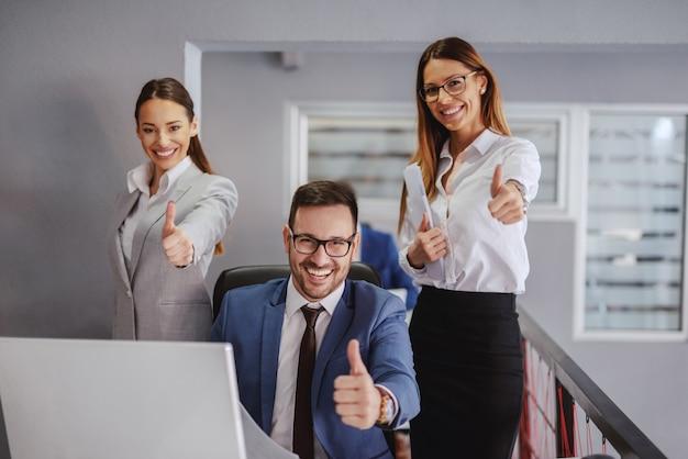 Homme d'affaires souriant assis et montrant les pouces vers le haut. deux collègues féminines debout à côté de lui et tenant les pouces vers le haut. intérieur de bureau. si vous faites ce que vous avez toujours fait, vous obtiendrez ce que vous avez toujours obtenu.