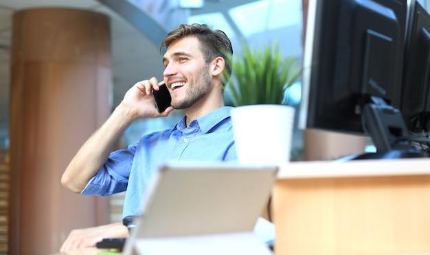 Homme d'affaires souriant assis et utilisant un téléphone portable au bureau