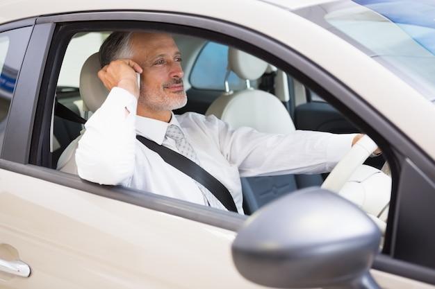 Homme d'affaires souriant au téléphone dans sa voiture