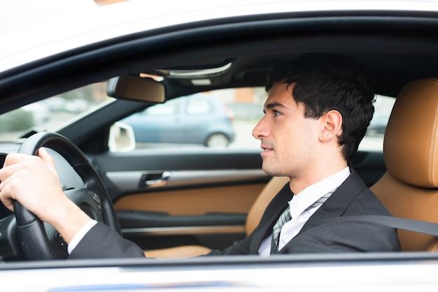 Homme d'affaires souriant au volant de sa nouvelle voiture blanche