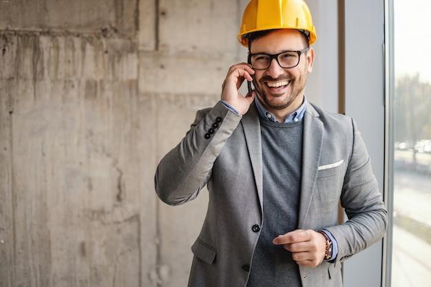 Homme d'affaires souriant avec casque sur la tête debout à côté d'une fenêtre dans le bâtiment en processus de construction et ayant un appel d'affaires