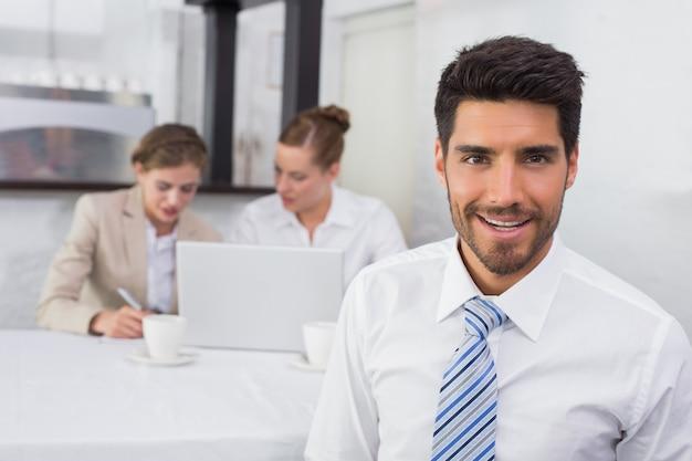 Homme d'affaires souriant avec des collègues au bureau