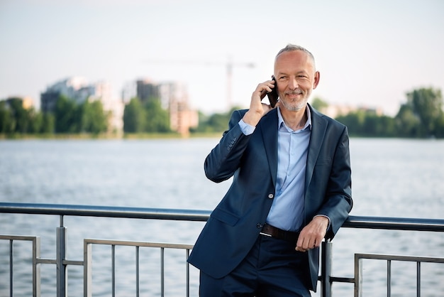 Homme d'affaires souriant en costume gris avec un smartphone.