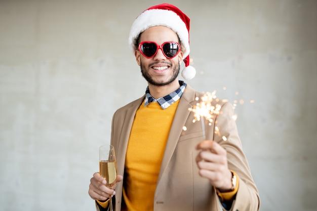 Homme d'affaires souriant dans des vêtements décontractés intelligents, une casquette de père noël et des lunettes de soleil en forme de cœur tenant une flûte de champagne et une lumière du bengale étincelante