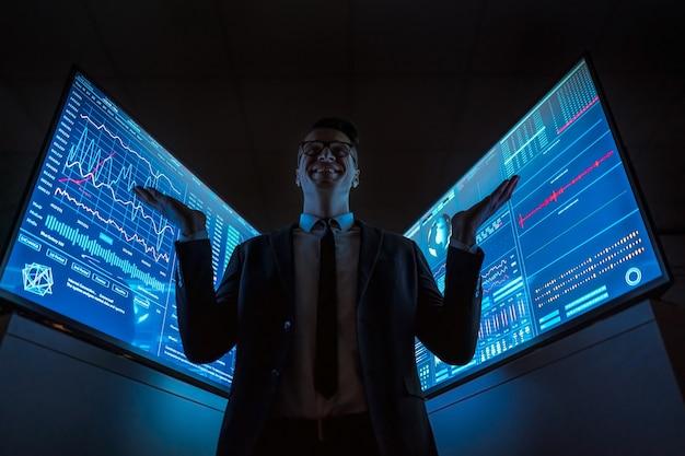 L'homme d'affaires souriant debout entre les écrans bleus dans le laboratoire sombre