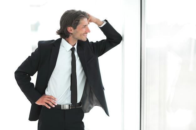 Homme d'affaires souriant debout près de la fenêtre au bureau. le concept de perspective.