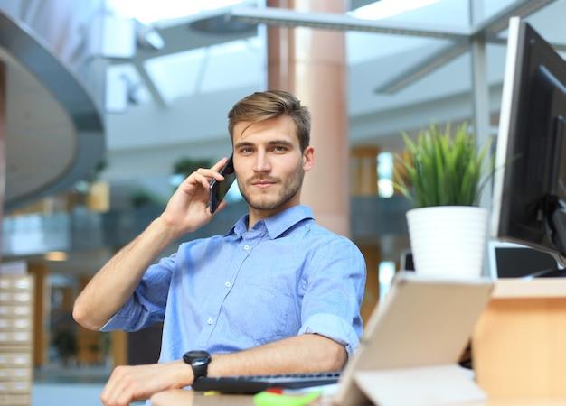 Homme d'affaires souriant debout et utilisant un téléphone portable au bureau