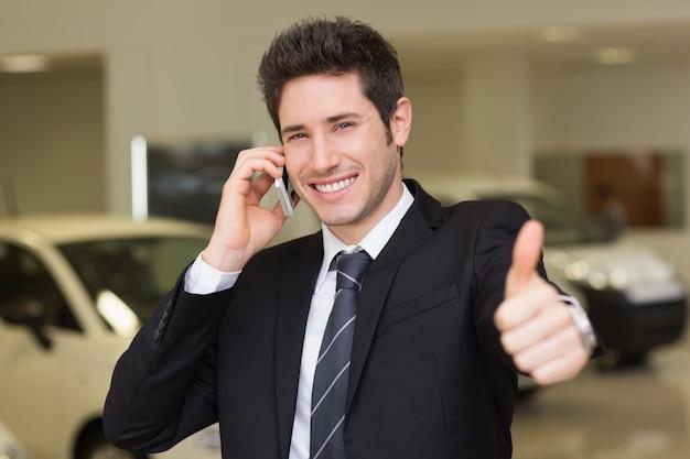 Homme d'affaires souriant donnant les pouces vers le haut sur le téléphone