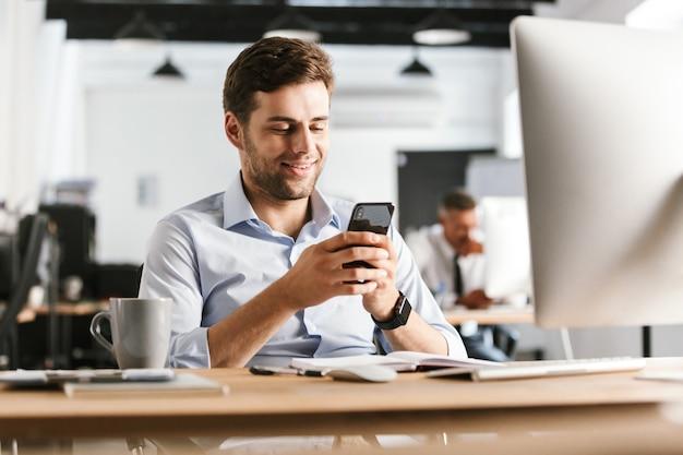 Homme d'affaires souriant, écrire un message sur smartphone alors qu'il était assis près de la table au bureau