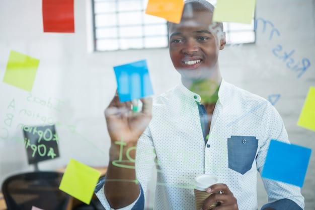 Homme d'affaires souriant, écrit sur des notes autocollantes